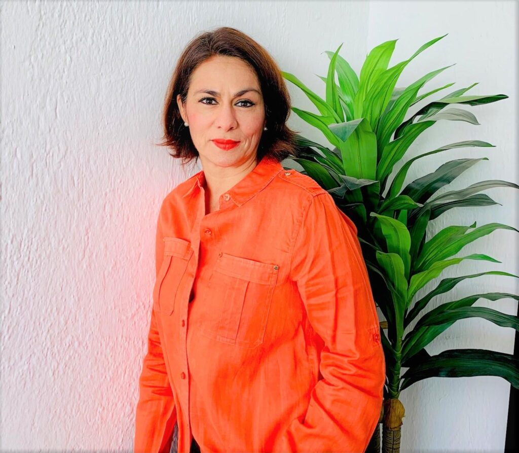 Flor Lopez, Site Director at HP Guadalajara, stares at the camera with a bright-orange blouse.